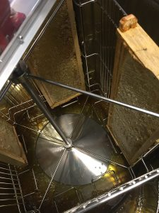 Photo of the inside of an extractor with frames and honey